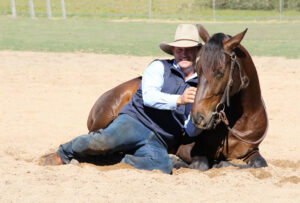 Guy McLean laying down with one of his horses